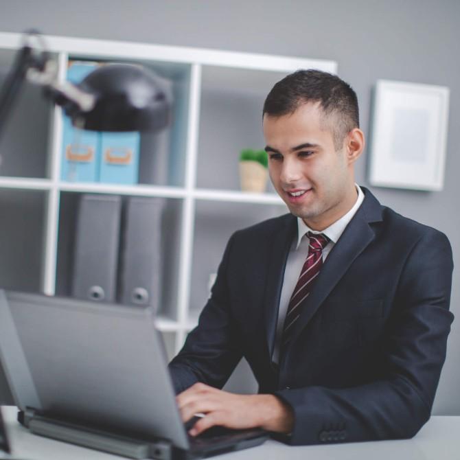 administração direta e indireta: homem jovem usando computador em escritório despojado