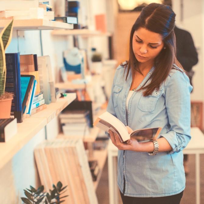 literatura: jovem mulher lendo livro em livraria de ambiente claro e organizado