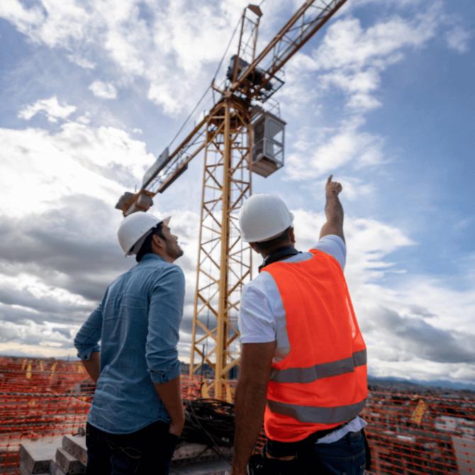 especialização em engenharia civil: dupla de engenheiros olhando obra em execução